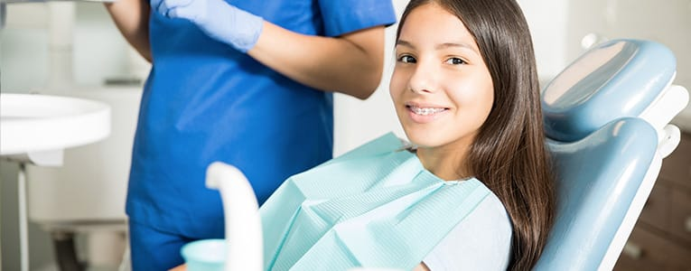 Female teenager sitting at dentist office